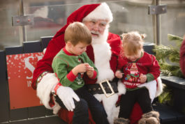 Two children sit on Santa's knees